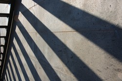 Shadow of the stairs reflected on the wall. Oblique lines, ladder isolated, sunny weather.