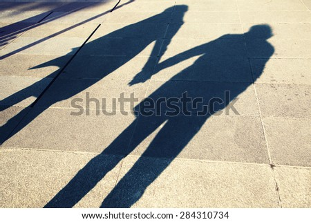 Shadow of two people holding hands on a walk in the city background, silhouette of two adult (girl and boy) holding hands at Sunset light. Two young people love each other.