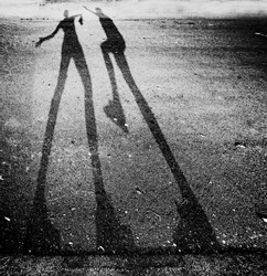 shadow of two people play fighting in the street toned with a high key filter effect
