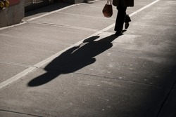 Shadow of unrecognizable businesswoman carrying a handbag on a deserted city street