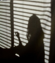 Shadow of young child against a cloth background in front of blinds; Child looking out a window with shadow cast on cloth background