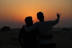 Shadow photo Two young man pointing hand towards sun set in desert, in red and orange backgrounded sky.