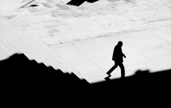 Shadow silhouette of a man walking alone down city stairs,  high angle view