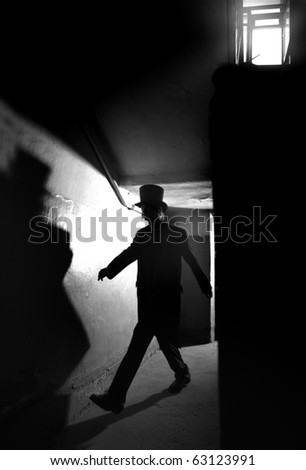 Shadowgraph of the man in black coat and hat going in the dark interior. Monochrome photo with natural darkness. Artistic grain added for movie effect