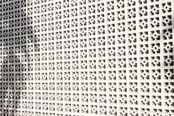Shadows fall on a white screen block wall arranged in a geometric pattern.