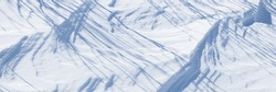 Shadows in the snow. Shadows from branches, bushes and trees on the snowy surface of the ground. Beautiful winter panoramic background.