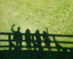 Shadows of four people on grass pavement.People shadows on the bridge, artistic photo with selective focus. Contrast, people shadows on sunny day on grass background, abstract photo.Meeting of friends