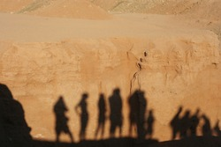 Shadows of people on a cliff in desert