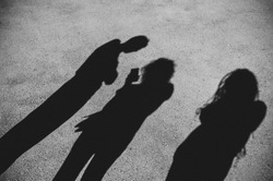 Shadows of people on pavement in black white