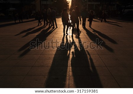 Shadows of people walking in a street of the city at the sunset.