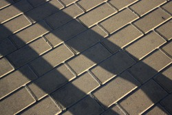 Shadows of the human legs on the yellow street paving tiles. Sunset
