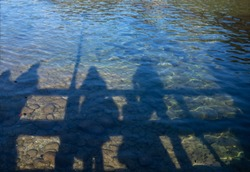 Shadows of the whole family, which are reflected in the Austrian lake, clear water, shimmering in the sun.
