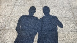 Shadows of two men on the cement floor one day.