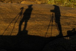 Shadows of two photographers with tripods cast on granite slab by setting sun