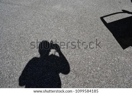 Shadows on the asphalt on a sunny day. The shadow of the photographer and the shadow of the car door. #1099584185