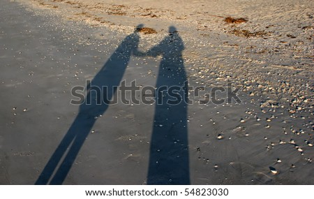 stock photo : shadows two people holding hands morning sun beach