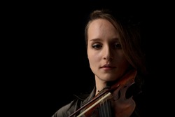 Shadowy portrait of a passionate woman playing a classical Baroque violin during a live musical performance or concert in a close up head shot with copy space