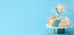 Shag cake with burned sparkler star on blue background. Colorful shag cake with perfect vanilla buttercream. Idea of visually striking cake decorating trendy cake, copy space. Long horizontal banner.
