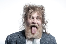 Shaggy adult gray-haired man with a beard wearing a gray suit shows tongue. Isolated