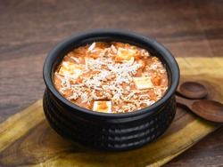 Shahi Paneer in Handi with wooden background