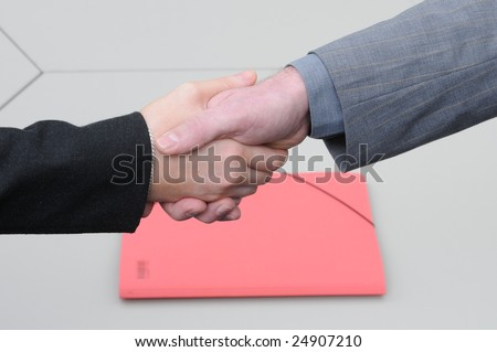 shake hands after successful agreement.Red file on the desk.