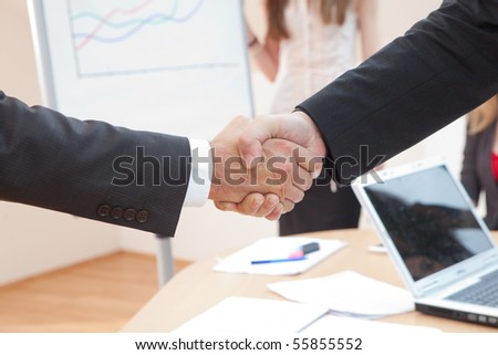 shake hands in the office with a laptop in the background - stock photo
