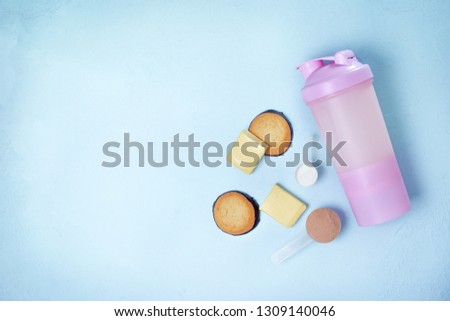 shake with protein drink, protein powder, protein bars and protein cookies on a blue background. view from above. copy space