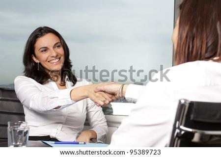 Shaking hands between two businesswomen
