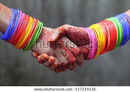 Shaking hands decorated with colorful bracelets and henna tattoo in Indian subcontinent