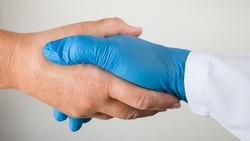 Shaking hands of healthcare professional with sick patient during COVID-19 pandemic. Safe handshake closeup on white background. Hand in blue protective glove and unprotected. Symbolic help or thanks.