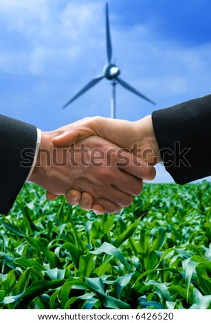 shaking hands with a wind mill in the background
