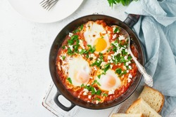 Shakshouka, eggs poached in sauce of tomatoes, olive oil, peppers, onion and garlic, Mediterranean cuisine. Keto meal, FODMAP recipe, low carb. Top view, copy space