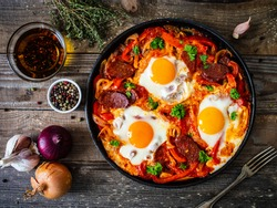 Shakshuka - fried eggs with chorizo and vegetables in frying pan