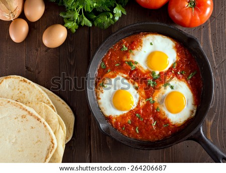 Shakshuka with eggs, tomato, and parsley in a cast iron pan. #264206687