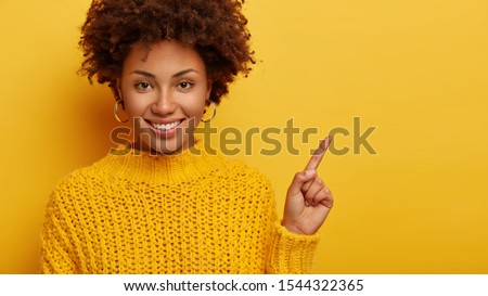 Shall we try it. Pleased curly haired woman with natural beauty, points index finger on blank space, going to check out new cafe, has glad look, wears warm cozy sweater, isolated over yellow wall stock photo