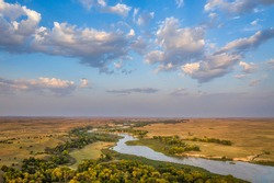 shallow and wide Dismal River flowing through Nebraska Sandhills at Nebraska National Forest, aerial view of afternoon scenery in early fall