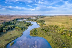 shallow and wide Dismal River meandering trough Nebraska Sandhills at Nebraska National Forest, aerial view of late summer or early fall scenery
