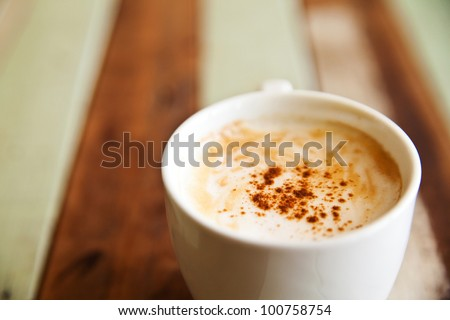 Shallow dept of field, a cup of coffee on wood background