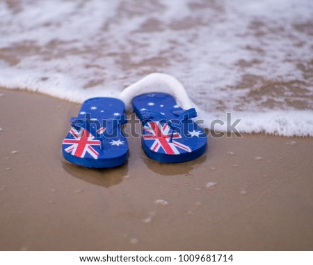 a2159fd1426 Shallow depth of field Australian flag thongs flip-flops washed up on a  sandy