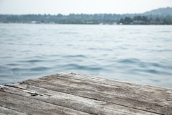 Shallow depth of field close up on an empty corner of a weather wood dock, with blurry lake water and distant shore in the background