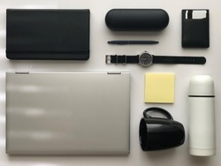 Shallow depth of field flat lay of telework office items with no focus on any object (black colors) - laptop, notebook, pen, watch, mask, hand sanitizer, mug, wallet, and case.