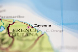 Shallow depth of field focus on geographical map location of Cayenne city French Guiana South America continent on atlas