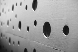 Shallow depth of field right side perspective of round black hole cut outs in a textured gray  plywood wall, with a random dot pattern in the background