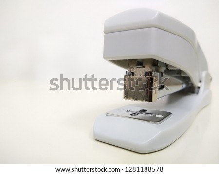 Shallow depth of field shot of a light grey stapler on table top against white background