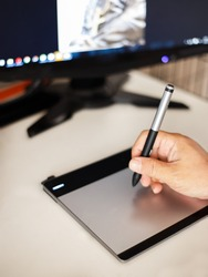 Shallow depth of field stylus drawing. A man holding the stylus pen drawing in front of the computer.