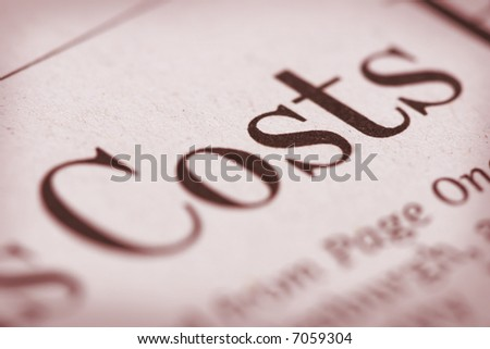 "Shallow depth of field with ""Costs"" and paper texture in focus."