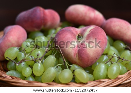 Shallow DOF composition of white grapes and donut peaches (one heart-shaped) in a wicker basket.  conceptual for harvest, late summer-early autumn and 'get well' wishes. #1132872437