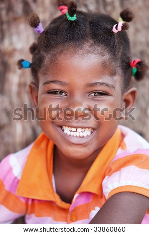 shallow DOF of African child with braids and orange tshirt