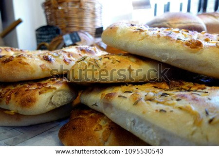 Shallow focus close up of rosemary and garlic focaccia bread, with other loaves in blurred background. #1095530543