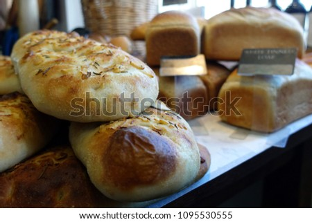 Shallow focus close up of rosemary and garlic focaccia bread, with other loaves in blurred background. #1095530555